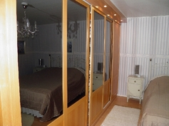 Makuuhuone, paikallisen huippupuusemän tilaan tekemä puinen liukuovikaapisto.