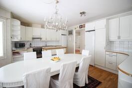 Isossa keittiössä runsaasti kaapistoja sekä työtasoa.
