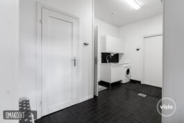 Tyylikkään tummalla laatoitetusta kodinhoitohuoneesta käynti wc:hen, pesuhuoneeseen sekä ulos.