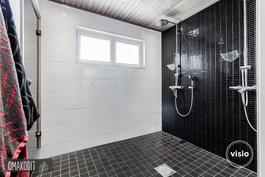 Myös pesuhuoneessa näyttävät laatoitukset, kaksi suihkua sekä lattialämmitys