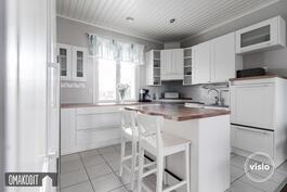 Vaaleassa keittiössä siistit pinnat, jääkaappi, pakastin, liesituuletin, korotettu astianpesukone.