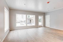 Olohuoneen lähes lattiaan asti olevat ikkunat tuovat valon ja luonnon esille