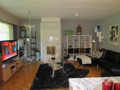 Näkymää kaksion ruokailutilasta olohuoneeseen päin ja kaksion olohuoneessa myös näyttävä keraaminen koristetakka ja ...