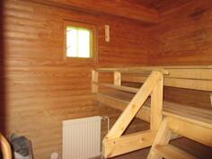 Kuvassa uima-allasosaston sauna, jossa pyöröhirsipaneeliseinät ja ...