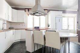 Saarekkeellinen, vaalea ja avara keittiö.