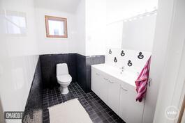 Erillisessä wc:ssä kauniit mustavalkoiset laatat ja valkoiset kaapit