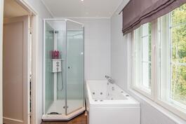 Yläkerran kylpyhuoneessa suihkukaappi ja poreamme