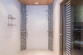 Saunan pesuhuoneessa kaksi sadesuihkua, lasiovi saunaan