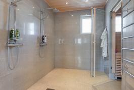 Tilava alakerran kylpyhuone / sauna -kokonaisuus.