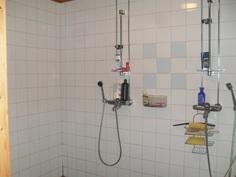 Laatoitetussa kylpyhuoneessa kaksi suihkua.