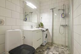 Tyylikäs kylpyhuone jossa myös pesukoneliitäntä.