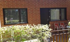Takapiha,vas. pienempi makuuhuone ja oikealla isomman makuuhuoneen ovi ja ikkuna.