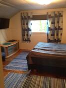 Yläkerran makuuhuone jossa myös pönttöuuni