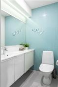 Alakerran wc:ssä on iso peili ja epäsuoraa valoa
