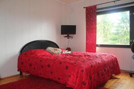 Valoisa makuuhuone, mistä kauniit näkymät rehevään puutarhaan