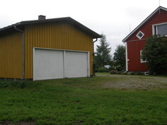 Autotallin sähkökäyttöiset nosto- ovet.  Rakennuksen toisessa päässä on naapurin lämpökeskus  ym.