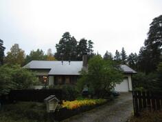 Talo ulkoapäin, kuvattuna pihatieltä, joka alempana kuin talo. Hämärä sadesää.