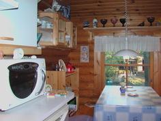 Honkarakenteen pyöröhirsimökin keittiö ja ruokailutilaa.