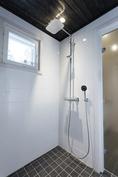Suihkutiloissa on tyylikästä vaaleaa kaakelia seinissä ja lattia ja seinäpinnat ovat tummat