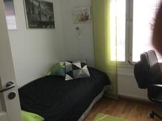 pieni makuuhuone, jossa kaksi kaappia oven takana