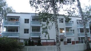 Rakennus ulkoa takapihalta, asunto vasemmalla ylhäällä.