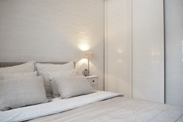 Makuuhuoneessa koko seinän levyinen Elfan säilytysjärjestelmä valkolasisten liukuovien takana