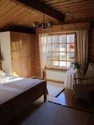 Yläkerran makuuhuone on avara ja ikkuna aukeaa parvekkeelle ja puutarhaan