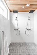 Pesuhuoneessa kaksi sadesuihkua vakiona. Kuva vastaavasta valmiista asunnosta.
