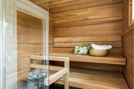 Sauna tornikiukaalla, lasiseinällä ja lämpöhaapapaneloinnilla. Kuva vastaavasta valmiista asunnosta