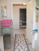 Kodinhoitohuone ja näkymä pesuhuoneeseen