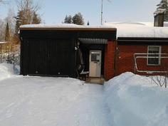 Näkymä autotallin ja valkoiseen oveen, josta pääsee ulkovälikköön, jossa vasta varsinainen ulko-ovi
