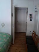 Näkymä pienestä makuuhuoneesta eteiseen päin, madallettu kynnys, vastapäätä näkyy kylpyhuoneen ovi