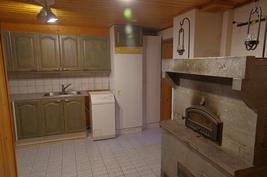Tilava kodinhoitohuone ja vuolukivinen leivinuuni kotiteatteritilasta nähtynä.