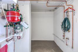 Lämmin varastotila jossa vuonna 2011 asennetut kaukolämpölaitteet ja uudet putkistot.