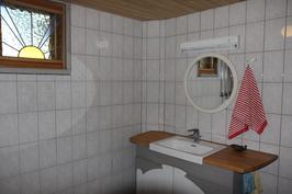 Saunan pesuhuoneen seinät on kaakeloitu ja tilassa on kaksi suihkua. Pöytätaso on pyökkiä.