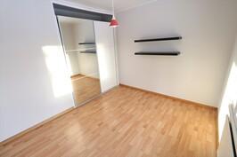Makuuhuoneen liukuovikomero upotettu seinän sisään, joten tila on tehokkasti käytössä.