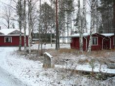 Päärakennus, mökit ja järvi tieltä