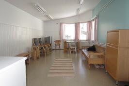 Kalustettu kerhohuone, joka sopisi hyvin vierashuoneeksikin.